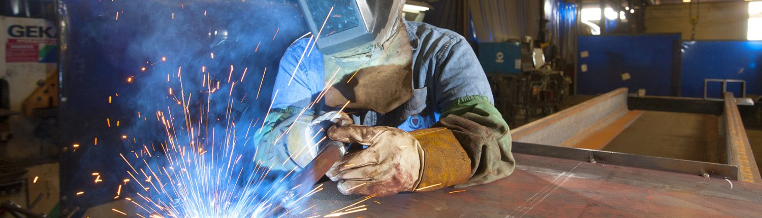 Image of a welder working to connect plates of steel. Image represents Fredricks Communications' extensive experience with manufacturing businesses in a wide range of industries, from renewable energy to farm implements to snow removal equipment.