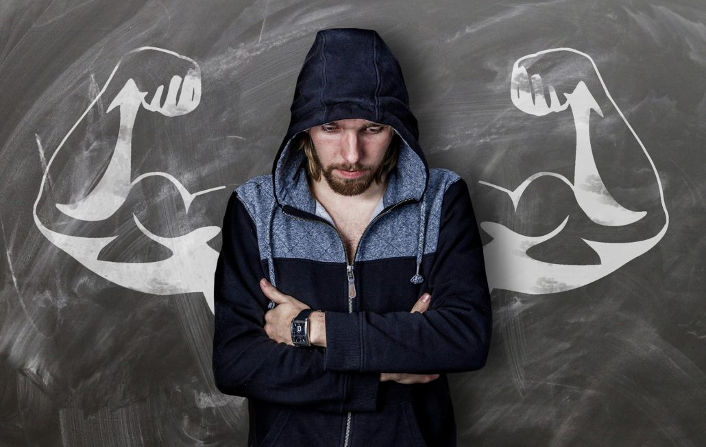 Man in front of blackboard with huge, muscular arms drawn on board